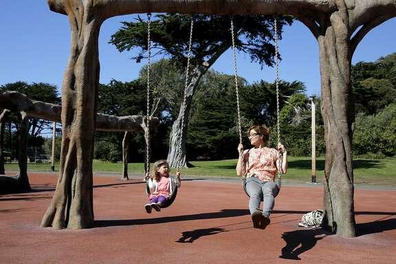 Meryl Press and Vida Huegel, 4, play on the swing set on the playground at the San Francisco Zoo in San Francisco, California, on Thursday, Sept. 17, 2015.