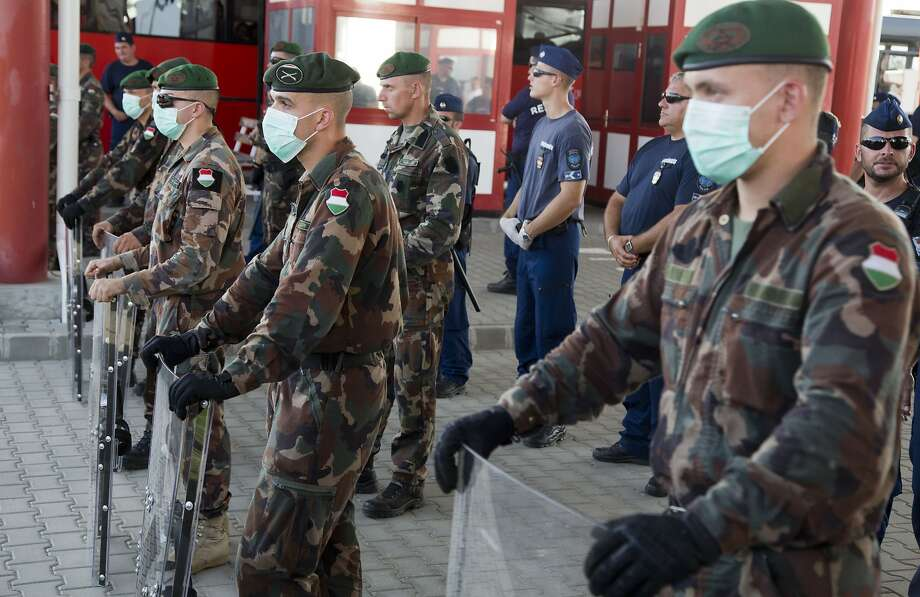 Hungarian soldiers and police stand guard at the border crossing in Beremend, Hungary, Friday, Sept. 18, 2015. Croatia has sent buses full of migrants to Hungary just hours after the country's prime minister said it could not cope with the influx. (AP Photo/Darko Bandic) Photo: Darko Bandic, Associated Press