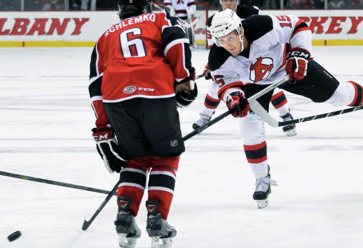 Albany Devils's #15 Paul Thompson, right, gets a shot past Portland Pirates' #6 David Schlemko during Saturday's game at the Times Union Center Dec. 6, 2014, in Albany, NY. (John Carl D'Annibale / Times Union)