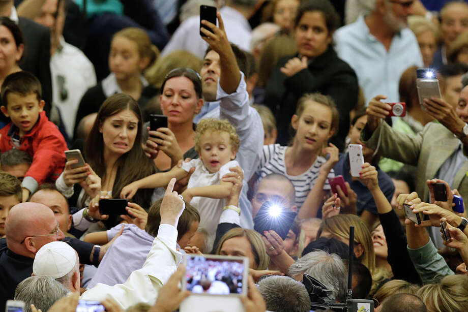 Pope Francis walks past a crowd of faithful and employees of the Rome's Cooperative Credit Bank during an audience in the Paul VI hall at the Vatican, Saturday, Sept. 12, 2015. (AP Photo/Gregorio Borgia) Photo: Gregorio Borgia / Associated Press / AP