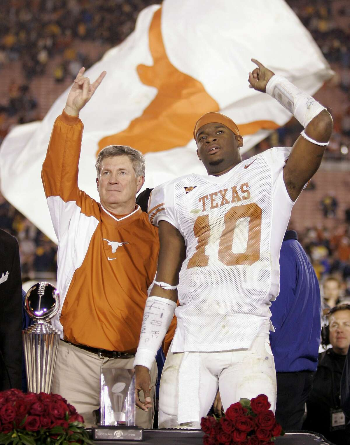 Texas head coach Mack Brown, left, and MVP Vince Young (10) celebrate with the Rose Bowl and MVP trophies after Texas beat Michigan, 38-37, in the Rose Bowl in Pasadena, Calif., Saturday, Jan. 1, 2005. (AP Photo/Mark J. Terrill) Ran on: 01-16-2005 Texas coach Mack Brown (left), with Rose Bowl MVP Vince Young, received a $22 million contract. The need for athletic departments to continually increase revenue has resulted in an inflated need to win.