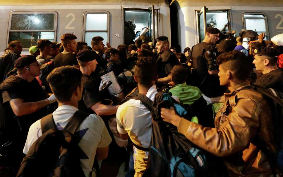 Migrants crowd to board a train Friday at the station in Tovarnik, Croatia. Croatia declared it was overwhelmed and began busing migrants in convoys back to Hungary and closing its border crossings with Serbia. Photo: Petr David Josek, STF / AP