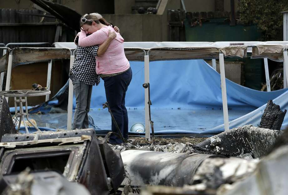 Deanna Hingst, right, embraces her mother Shirley Leuzinger as they stand at the family's destroyed home Monday, Sept. 14, 2015, in Middletown, Calif. Two of California's fastest-burning wildfires in decades overtook several Northern California towns, killing at least one person and destroying hundreds of homes and businesses and sending thousands of residents fleeing highways lined with buildings, guardrails and cars still in flames. (AP Photo/Elaine Thompson) Photo: Elaine Thompson, Associated Press