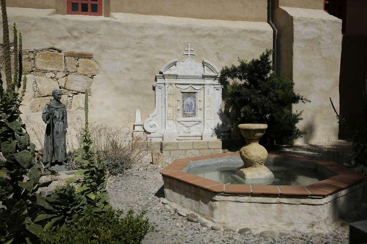 A statue of Junipero Serra (left) is seen in the Serra Prayer Garden at Mission San Carlos Borromeo del Rio Carmelo on Thursday, September 17, 2015 in Carmel-By-The-Sea, Calif.