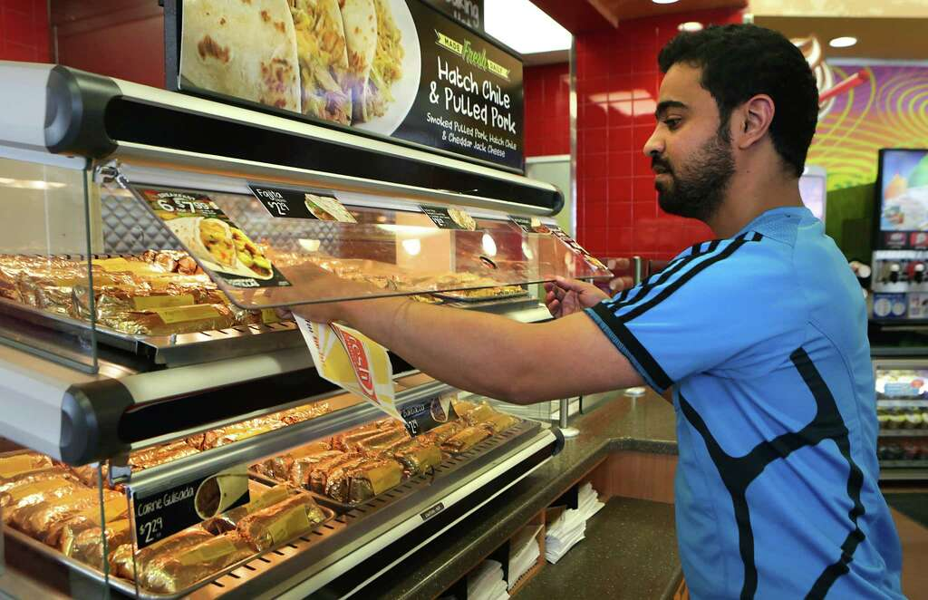 UTSA student Sultan Aladhyani grabs a fajita taco from a warmer at the Corner Store at  Grocery style foods