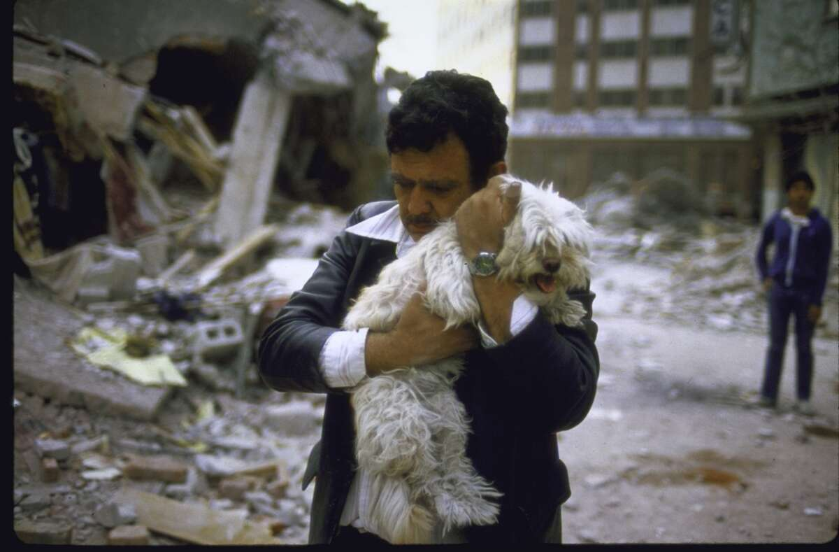 A man hugs his dog after his 2 children died in the 1985 earthquake.