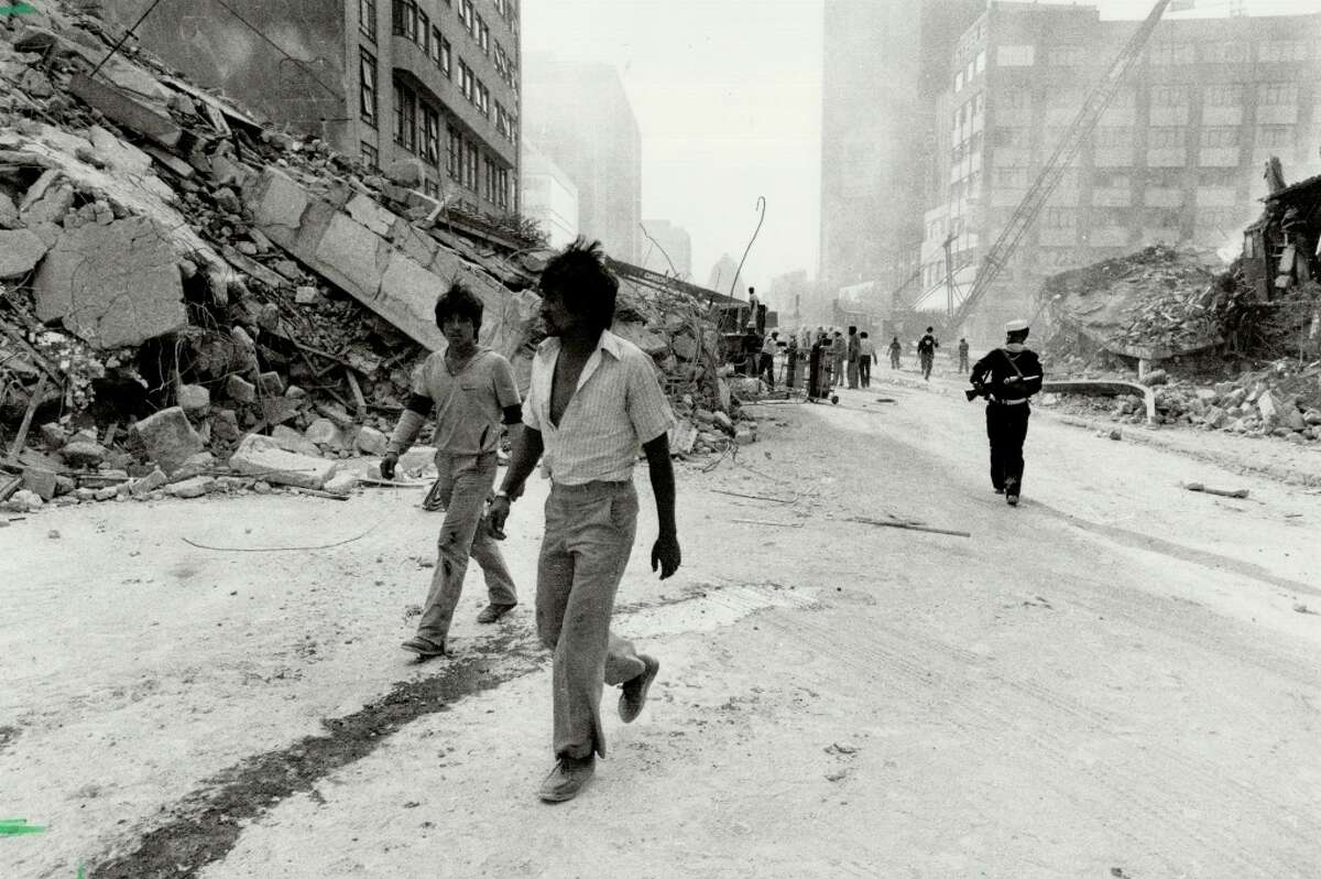 City in chaos: A Mexican sailor (right); rifle at the ready; keeps an eye out for looters as still-dazed residents of Mexico City explore the ruins of their historic city in the wake of two major earthquakes in 48 hours in September 1985.