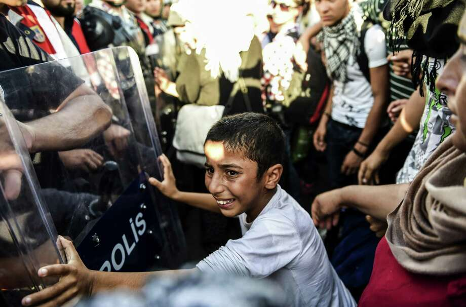 TOPSHOTS A boy pushes against a police barricade as Syrian refugees and migrants  as they march along the highway towards the Turkish-Greek border at Edirne on September 18, 2015.  Several hundred migrants who have been blocked by police in northwest Turkey from crossing overland into Greece drew closer to the border after the authorities briefly opened the route. From their makeshift camp on the outskirts of the border city of Edirne the migrants -- mostly Syrian refugees -- began walking in the direction of the city centre, beyond which lies the road to Greece, an AFP photographer reported.  AFP PHOTO/BULENT KILICBULENT KILIC/AFP/Getty Images Photo: BULENT KILIC, Staff / AFP / Getty Images / AFP