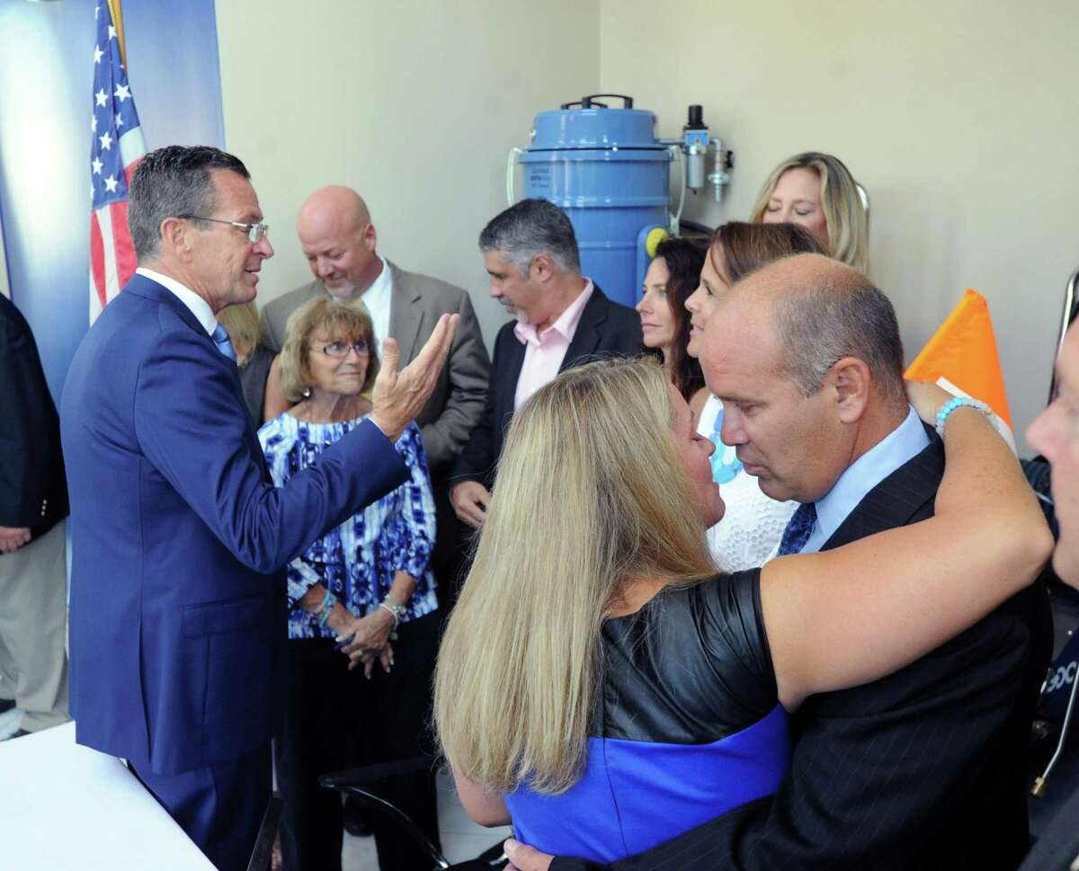 Pam Fedorko, center, and Joe Fedorko, right, the parents of Emily Fedorko, embrace after Gov. Dannel P. Malloy, left, signed a safe boating and towing law at Goodway Technologies Corporation in Stamford Friday.