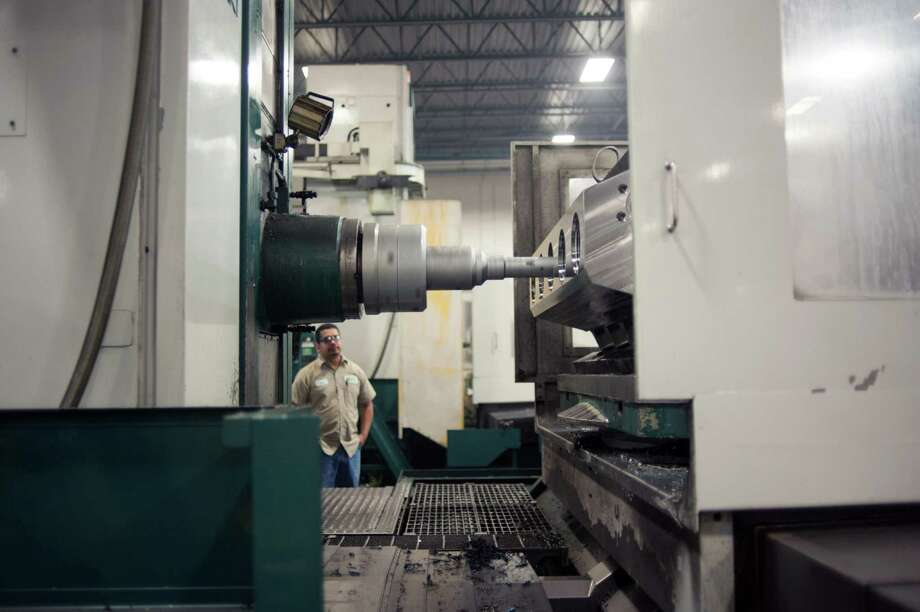 A horizontal boring mill bores into what will be a part for a high-pressure pump used for hydraulic fracturing at FTS International's Fort Worth manufacturing facility. The Dallas Fed's survey, based on responses from 116 Texas manufacturers, showed an increase in production for December. But its company outlook index, which measures whether manufacturers think their companies have better days ahead, declined sharply, to minus 9.7 this month from 0.8 in November. Photo: Houston Chronicle File Photo / 2014 Houston Chronicle