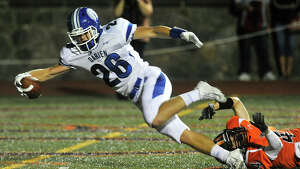 Darien's Nick Green scores a touchdown while being tripped up by Stamford's Mark Serricchio during their football game at Stamford High School in Stamford, Conn., on Friday, Sept. 18, 2015. Darien won, 47-14.