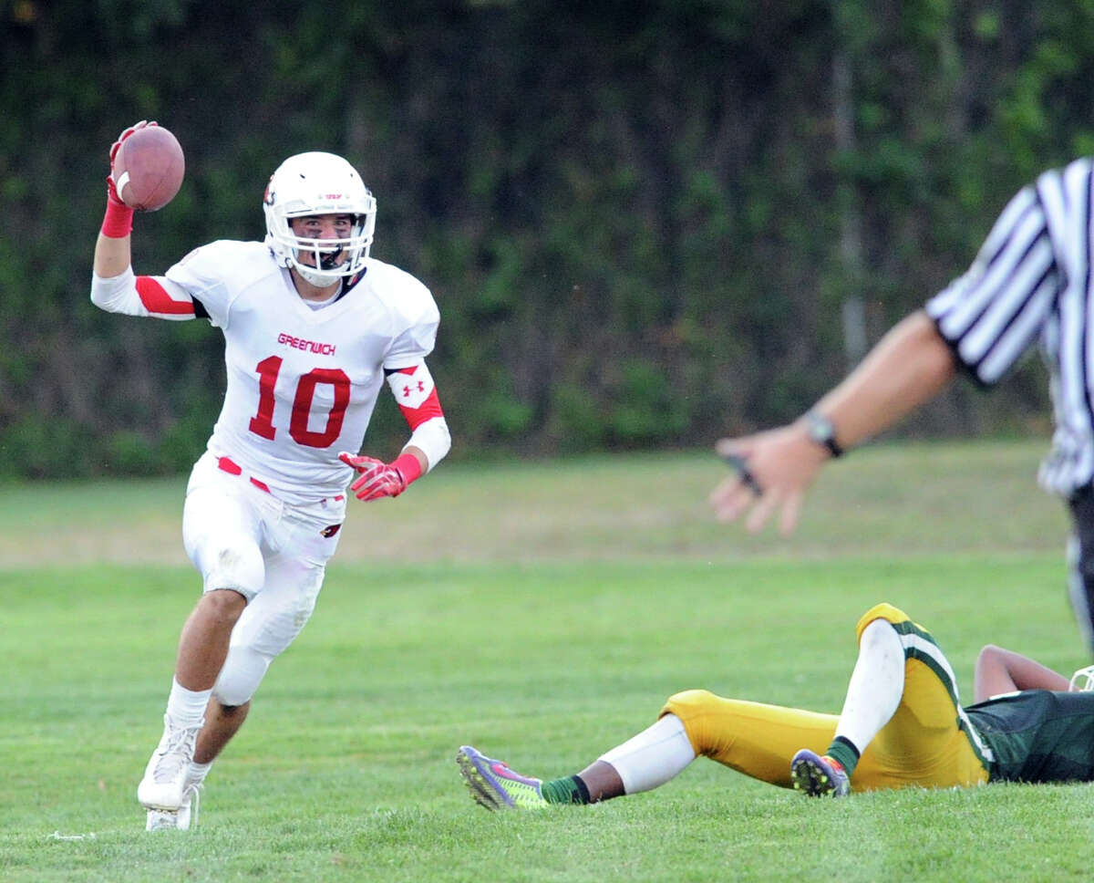 Connor Langan of Greenwich holds up the ball after making an interception in the final minute of play to seal the victory for Greenwich during the high school football game between Trinity Catholic High School and Greenwich High School at Trinity in Stamford, Conn., Friday, Sept. 18, 2015. Greenwich won the game, 42-38.