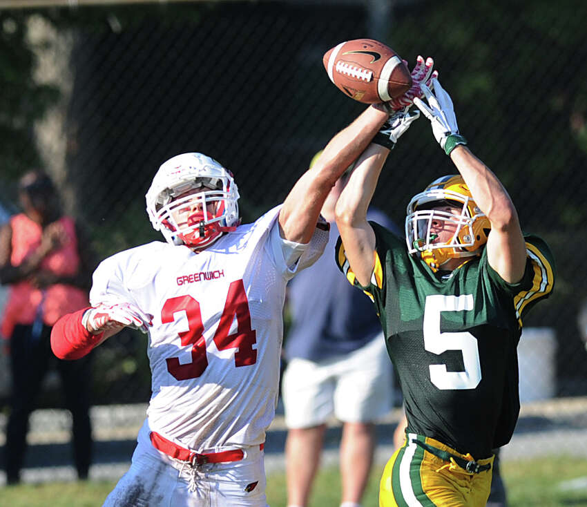 Greenwich defender Mike Gianesello (#34), left, breaks up a pass thrown to Trinity's Dominick Svrcek (#5), right, during the high school football game between Trinity Catholic High School and Greenwich High School at Trinity in Stamford, Conn., Friday, Sept. 18, 2015. Greenwich won the game, 42-38.