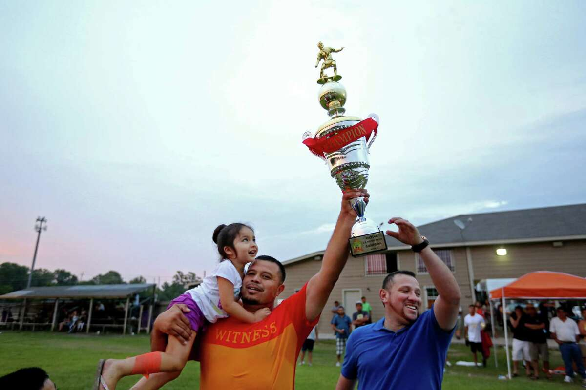 Coach Luis Paredes celebrates his team's championship with his 3-year-old daughter, Sofia. Paredes happily spends hours every weekend traveling to soccer games in the region.