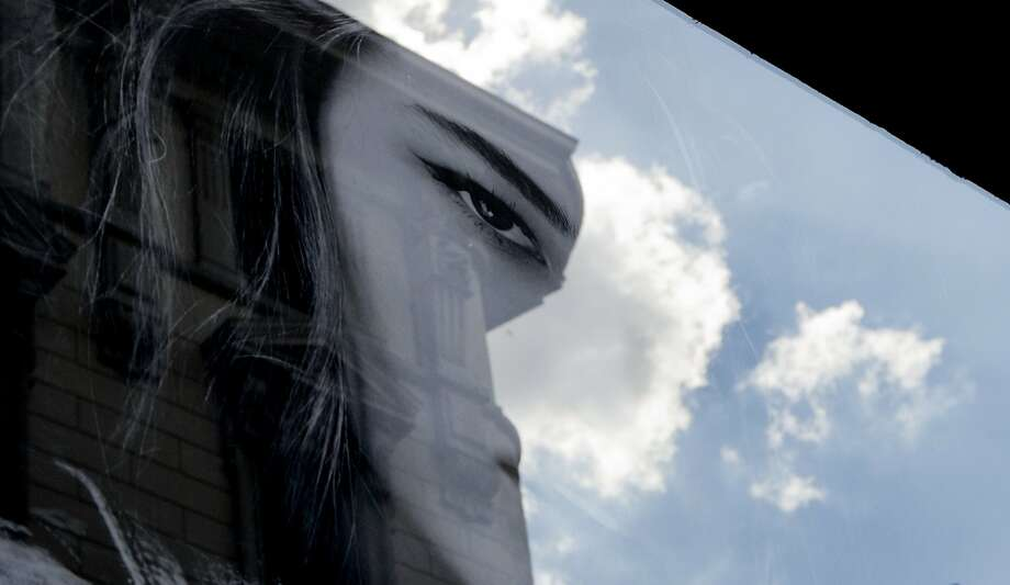 Clouds are reflected in the window of a clothes shop displaying a poster of a model, in Milan, Italy, Friday, Sept. 18, 2015. Photo: Luca Bruno, Associated Press