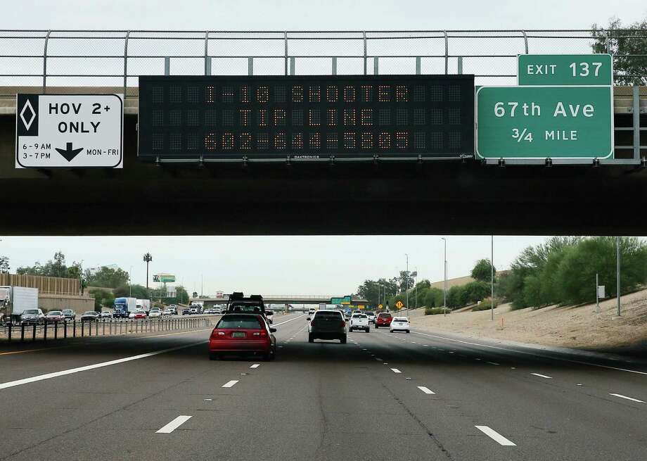 FILE - In this Sept. 10, 2015, file photo, a tip line for motorist hangs on a freeway sign along Interstate 10, in Phoenix. A suspect has been arrested in a string of shootings along Phoenix-area freeways that have kept drivers on edge, state officials said Friday, Sept. 18. (AP Photo/Matt York, File) Photo: Matt York, STF / ap