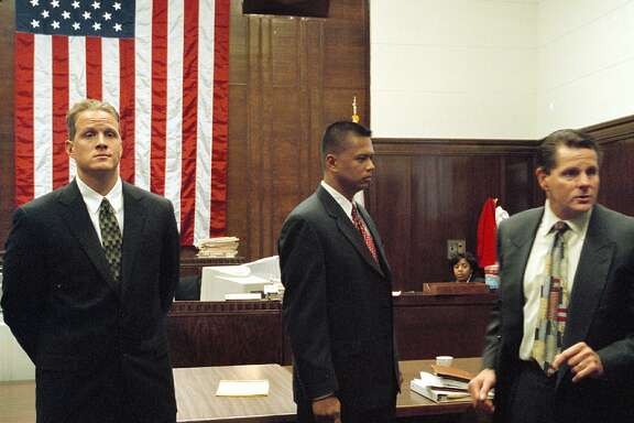 "Matthew Hornung, left, and Clarence ""Chuck"" Mabanag, center, two of four former Oakland police officers known as ""The Riders,"" and defense attorney Michael Rains are shown during a recess in the first day of the former officers' trial Thursday, Sept. 12, 2002, at Alameda County Superior Court in Oakland, Calif. A third officer, Jude Siapno, is also on trial while the fourth,  Frank Vazquez, remains fugitive. A prosecutor in the case said the officers systematically set up young black men and conjured false accusations against them to feed their egos. (AP Photo/The Oakland Tribune, Ray Chavez). Also ran 08/31/03"