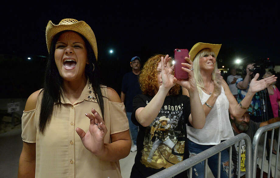From left, fans Jessica LeJeune, her sister-in-law Dana LeJeune, and Annette Howard dance and sing along as Southeast Texas native and country music hall of fame inductee Tracy Byrd performs Friday night at the Orange Pavilion. The show, followed by fireworks, helps kick off the weekend's SPORT tunnel boat races on the Sabine River.