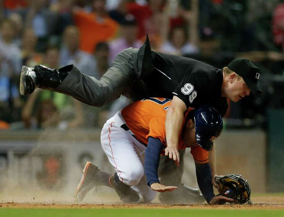 Houston Astros second baseman Jose Altuve (27) collides with home plate umpire Toby Basner as Oakland Athletics catcher Carson Blair (39) tried to tag him out on a Jed Lowrie sac fly during the third inning of an MLB baseball game at Minute Maid Park on Friday, Sept. 18, 2015. ( Karen Warren / Houston Chronicle ) Photo: Karen Warren, Staff / © 2015 Houston Chronicle