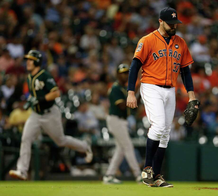 Astros relief pitcher Pat Neshek, right, can't bear to watch as the Athletics' Danny Valencia rounds the bases after hitting a  decisive two-run homer in the eighth inning Friday night at Minute Maid Park. Photo: Karen Warren, Staff / © 2015 Houston Chronicle