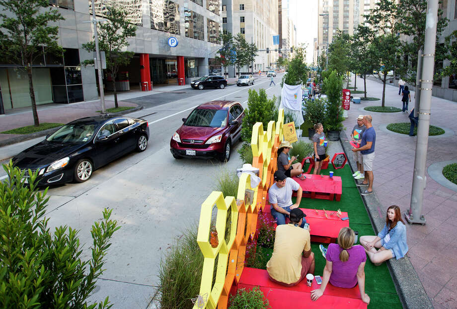 From PARK(ing) Day 2015: Members of the SWA Group sit in their converted parking space in downtown Houston. Photo: Cody Duty, Houston Chronicle / © 2015 Houston Chronicle