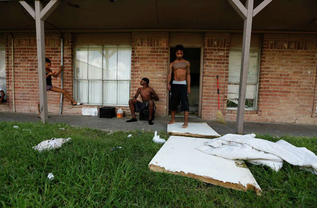 Kevin Turner stands on what is left of his front door as neighbors Pernice Brown (left) and Chase Russell (center) talk outside the Turner's apartment Friday, Sept. 18, 2015, in Houston. Kevin's brother Jamarcus Turner said when they moved in the front door was off its hinges and management wouldn't repair it.