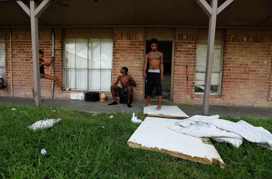 """Kevin Turner  stands on what is left of his front door as neighbors Pernice Brown (left) and Chase Russell  (center) talk outside the Turner's apartment Friday, Sept. 18, 2015, in Houston. Kevin's brother Jamarcus Turner said when they moved in the front door was off its hinges and management wouldn't repair it. """"Now its on the ground and we have no way of securing our stuff"""" Jamarcus said about his situation at the Crestmont Apartments 5602 Selinsky Road.  Mayor Parker held a news conference Thursday to announce the city is intervening to help the residents of the rundown Crestmont Apartments on Selinsky at Martin Luther King Drive. The tenants have been without power because the landlord has refused to pay the bill. This has created a public safety emergency for the residents. The City is arranging to get the power turned back on and has asked the Red Cross to help with food and water for the time being. The City is working to find new housing for the tenants. Photo: Steve Gonzales, Houston Chronicle / © 2015 Houston Chronicle"""