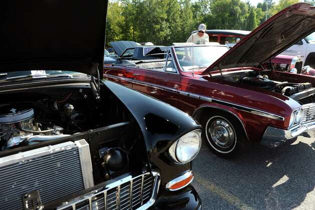 Bill Traver of Round Lake, right, checks out his 1964 Buick Skylark convertible during the 5th annual Times Union Car show to benefit the Hope Fund on Saturday, Sept. 19, 2015, at the Times Union in Colonie, N.Y. At left is a 1955 Chevy Bel Air. (Cindy Schultz / Times Union) Photo: Cindy Schultz / 00033392A3