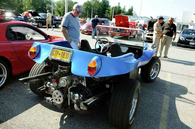 Charlie Brennan of Colonie, center, looks over a 1968 California Clipper, a Volkswagen dune buggy, during the 5th annual Times Union Car show to benefit the Hope Fund on Saturday, Sept. 19, 2015, at the Times Union in Colonie, N.Y.  (Cindy Schultz / Times Union) Photo: Cindy Schultz / 00033392A3