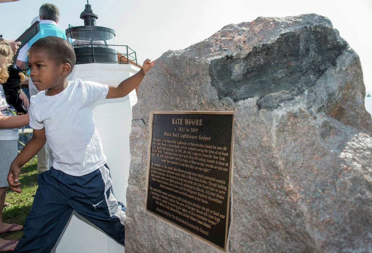Ayden Malcolm walks by the stone monument dedicated to the memory of Kate Moore, a 19th Century lighthouse keeper during a ceremony held by the the History Committee of the Black Rock Community Council to dedicate the large stone monument placed at historic St Mary's by the Sea Bridgeport, CT. Saturday, September 19, 2015.