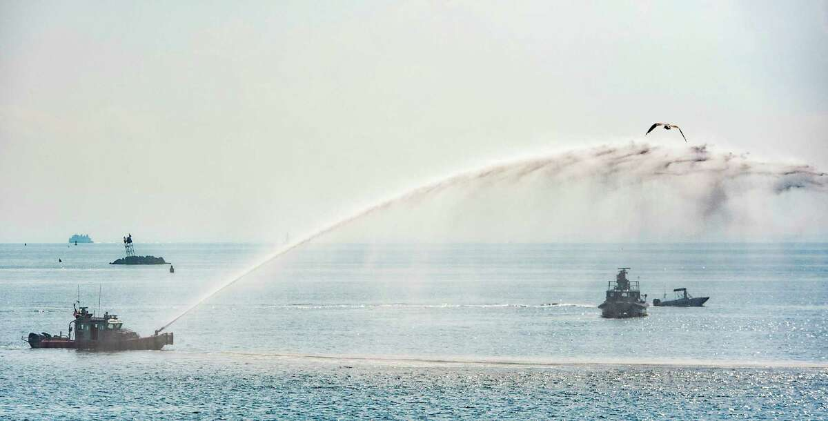 A fireboat sprays a stream of water during the ceremony held by the The History Committee of the Black Rock Community Council to dedicate a large stone monument placed at historic St Mary's by the Sea Bridgeport, CT to honor the memory of Kate Moore, a 19th Century lighthouse keeper. Saturday, September 19, 2015.