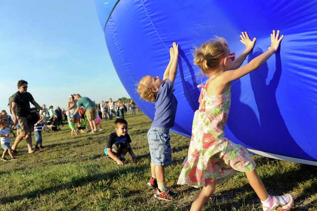 Griffin Braidwood, 2, of Queensbury, center, and his sister Sophia Braidwood, 4, right, touch the sides of a hot air balloon as it fills with air during the Adirondack Balloon Festival on Friday, Sept. 18, 2015, at Floyd Bennett Memorial Airport in Queensbury, N.Y. Flight times are 6:30 a.m. and 5 p.m. on Saturday and Sunday.(Cindy Schultz / Times Union) Photo: Cindy Schultz / 00033270A