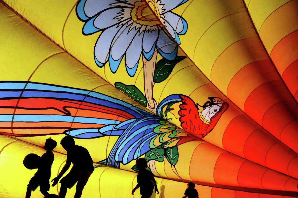 Children play inside a filled balloon that's no longer flight worthy during the Adirondack Balloon Festival on Friday, Sept. 18, 2015, at Floyd Bennett Memorial Airport in Queensbury, N.Y. The On Your Way Up Ballooning company of Quakertown, Penn. charges $2 to experience being inside of a balloon. Flight times are 6:30 a.m. and 5 p.m. on Saturday and Sunday.(Cindy Schultz / Times Union)