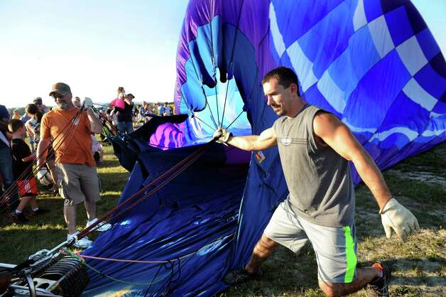 Jason Rosick of Hudson Falls, right, and Jeff Sherlock of Glens Falls, left, hang on to the opening of a hot air balloon as it's filled with air during the Adirondack Balloon Festival on Friday, Sept. 18, 2015, at Floyd Bennett Memorial Airport in Queensbury, N.Y. Flight times are 6:30 a.m. and 5 p.m. on Saturday and Sunday.(Cindy Schultz / Times Union) Photo: Cindy Schultz / 00033270A