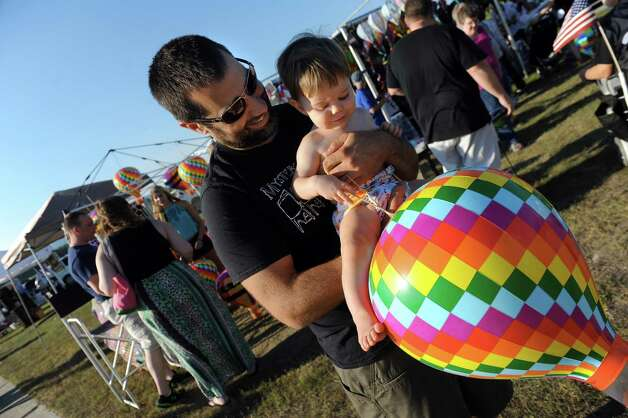Ian Sogoian, 11-months old, of Niskayuna carries a small version of a hot air balloon with help from his dad, Mike Sogoian, during the Adirondack Balloon Festival on Friday, Sept. 18, 2015, at Floyd Bennett Memorial Airport in Queensbury, N.Y. Flight times are 6:30 a.m. and 5 p.m. on Saturday and Sunday.(Cindy Schultz / Times Union) Photo: Cindy Schultz / 00033270A