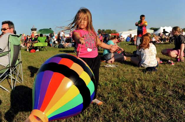 Madelynn Hofmann, 5, of Queensbury, center, plays with a toy hot air balloon during the Adirondack Balloon Festival on Friday, Sept. 18, 2015, at Floyd Bennett Memorial Airport in Queensbury, N.Y. Flight times are 6:30 a.m. and 5 p.m. on Saturday and Sunday.(Cindy Schultz / Times Union) Photo: Cindy Schultz / 00033270A