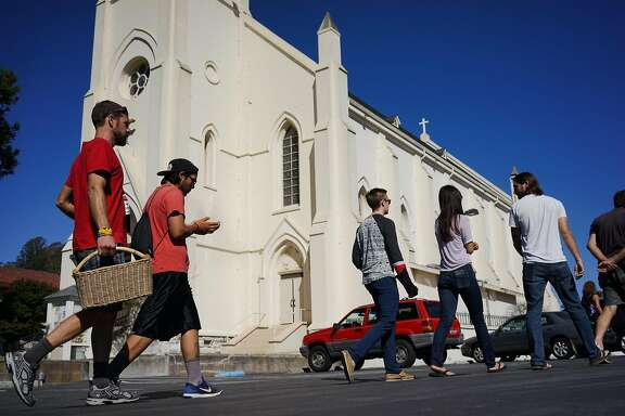 Greg Cotten, left, and Kagen Holland, second from left, walk to the parking lot of Holy Cross Church where a mass grave for Native Americans is in Santa Cruz, Calif. on Saturday Sept. 19, 2015. Tataviam descendants Caroline Ward Holland and Kagen Holland are leading the Walk for the Ancestors which will visit every mission in protest of the canonization of Junipero Serra.