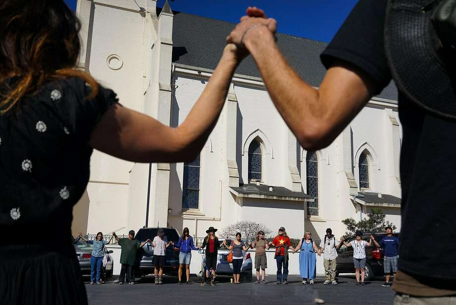 Community members gather for a prayer for Native Americans who were buried in the parking lot of Holy Cross Church in Santa Cruz, Calif. on Saturday Sept. 19, 2015. Tataviam descendants Caroline Ward Holland and Kagen Holland are leading the Walk for the Ancestors which will visit every mission in protest of the canonization of Junipero Serra. Photo: James Tensuan, Special To The Chronicle