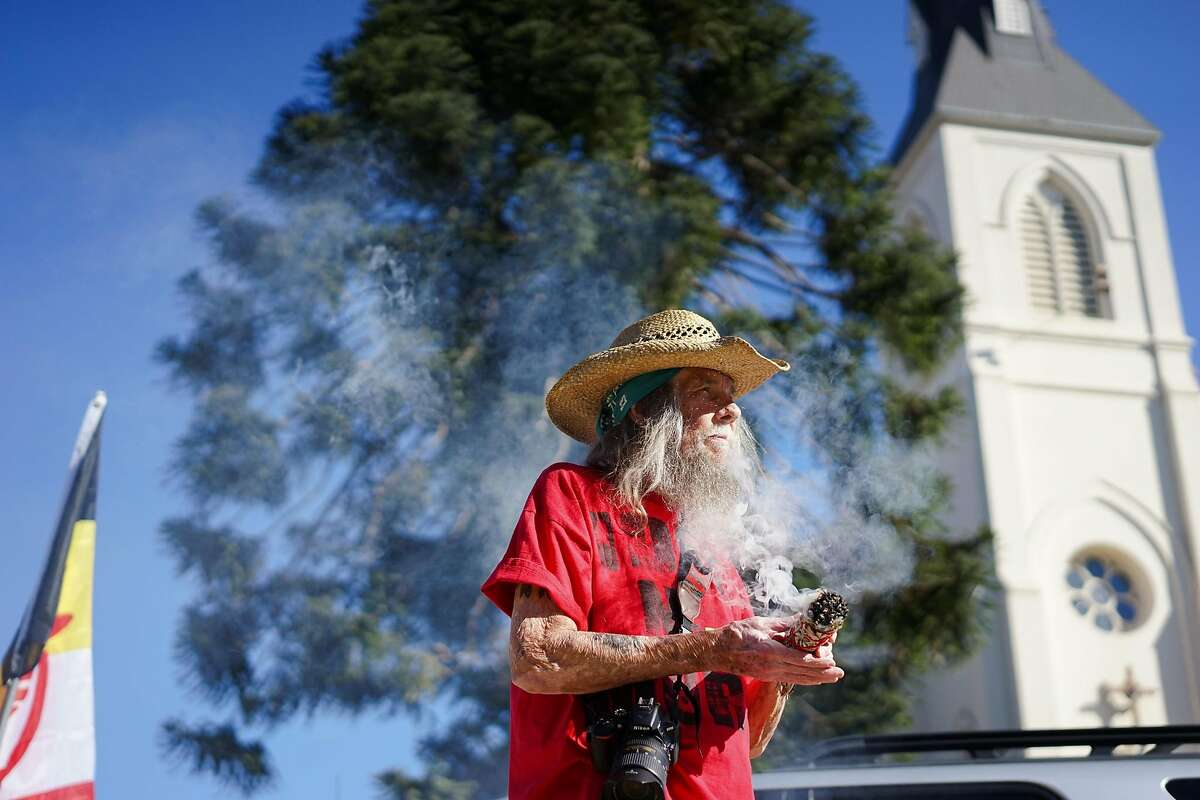 Autumn Sun cleanses himself with sage at Holy Cross Church in Santa Cruz, Calif. on Saturday Sept. 19, 2015. Tataviam descendants Caroline Ward Holland and Kagen Holland are leading the Walk for the Ancestors which will visit every mission in protest of the canonization of Junipero Serra.