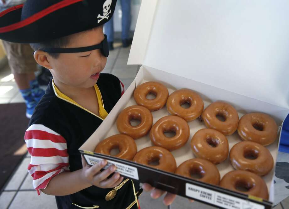 Tyler Quan, 5, admires his booty of doughnuts at the Krispy Kreme in Daly City, Calif. on Saturday, Sept. 19, 2015. Any customer dressed with three or more pirate items received a dozen Krispy Kreme doughnuts for free to celebrate International Talk Like A Pirate Day and anyone who simply talked like a pirate received a single doughnut for free. Photo: Paul Chinn, The Chronicle
