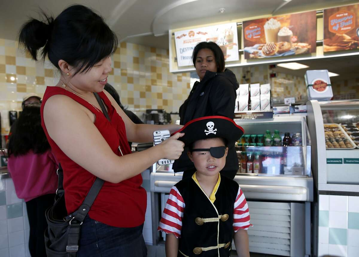 Jennifer Quan adjusts her son Tyler's pirate outfit before scooping up free doughnuts at the Krispy Kreme in Daly City, Calif. on Saturday, Sept. 19, 2015. Any customer dressed with three or more pirate items received a dozen Krispy Kreme doughnuts for free to celebrate International Talk Like A Pirate Day and anyone who simply talked like a pirate received a single doughnut for free.