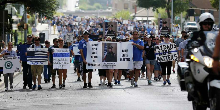 Supporters of the Police Lives Matter rally make their way up 8th Street as they head toward the state capital in Austin on Saturday, Sept. 19, 2015. About 3,000 people had signed up to participate in the rally that showed support for law enforcement officers and for their fallen comrades like Harris County Sheriff's Deputy Darren Goforth who was killed at gas station in August and for Hutto Police Sgt. Chris Kelley who was killed when he was ran over by his own vehicle by a man he pulled over for a traffic stop in June. The Police Lives Matter rally culminated in a moment of silence and prayer on the steps of the Capital and then concluded. A rally held by organizers of Black Lives Matter was also held on the opposite side of the Capital at the same time but there was little to no interaction between the two groups. Photo: Kin Man Hui, San Antonio Express-News / ©2015 San Antonio Express-News