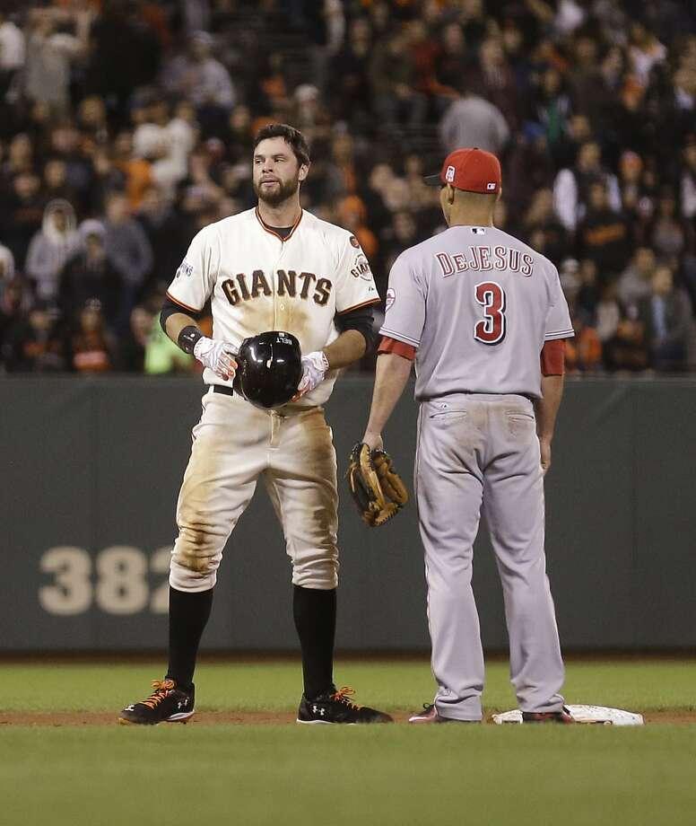 Reds infielder Ivan De Jesus checks on Brandon Belt after accidentally kneeing the Giants in the helmet Sept. 15, causing his latest concussion. Photo: Ben Margot, Associated Press
