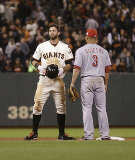 Cincinnati Reds' Ivan De Jesus, right, checks on the condition of San Francisco Giants' Brandon Belt after the two men collided at second base in the sixth inning of a baseball game Tuesday, Sept. 15, 2015, in San Francisco. (AP Photo/Ben Margot)