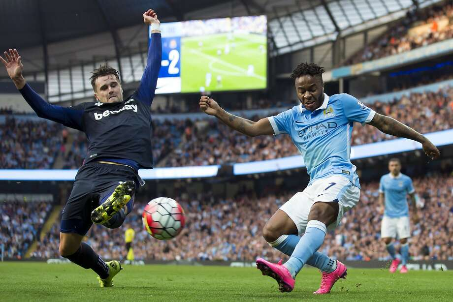 Manchester City's Raheem Sterling (right) has a cross blocked by West Ham's Carl Jenkinson as City, the English Premier League leader, lost its first match. Photo: Jon Super, Associated Press
