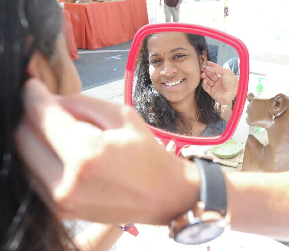Stamford resident Sindhu Gada tries on an earring being sold by L'Harmonie Jewelry during the Arts & Crafts on Bedford Street in Stamford, Conn., Saturday, Sept. 19, 2015. Photo: Bob Luckey Jr. / Hearst Connecticut Media / Greenwich Time