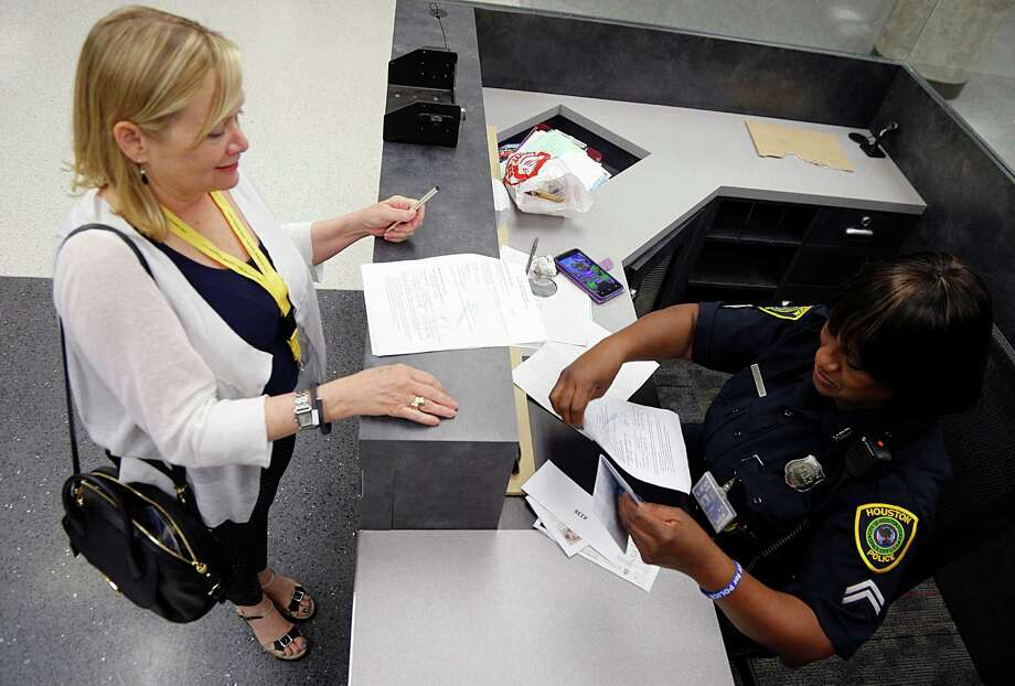 The Houston Police Department's Mary Boozier right, looks over documents from Kathleen Boyd , at U.S. Customs and Border Protection check point during testing of processes and the different facilities at Hobby Airport's new international concourse set to open in October,  Saturday, Sept. 19, 2015, in Houston. About 250 volunteers will get passports, boarding passes, to test the new concourse facilities. Photo: James Nielsen, Houston Chronicle / © 2015  Houston Chronicle