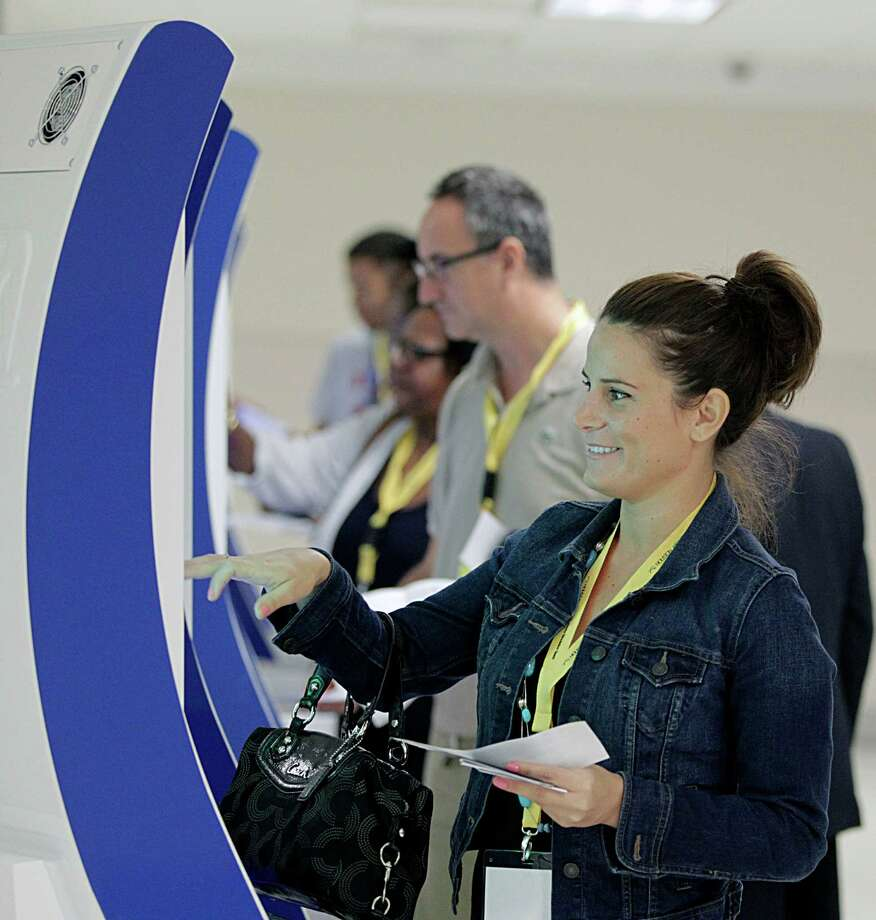 Anne Lewandowski uses an Automated Passport Control terminal during testing of processes and the different facilities at Hobby Airport's new international concourse set to open in October,  Saturday, Sept. 19, 2015, in Houston. About 250 volunteers will get passports, boarding passes, to test the new concourse facilities. Photo: James Nielsen, Houston Chronicle / © 2015  Houston Chronicle