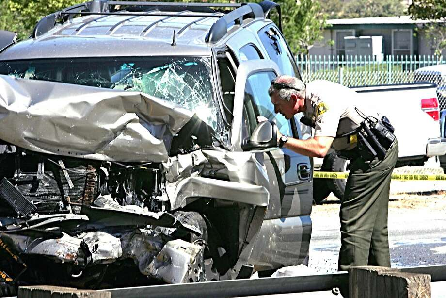 A deputy checks an SUV involved in a crash on Interstate 215 at the Little League Drive freeway overpass in San Bernardino, Calif., Friday, Sept. 18, 2015. Authorities say a wrong-way freeway driver has died in California after being shot at from a San Bernardino County sheriff's helicopter during a chase. (Richard Brooks/The Press-Enterprise via AP) MAGAZINES OUT; MANDATORY CREDIT; LOS ANGELES TIMES OUT Photo: Richard Brooks, Associated Press