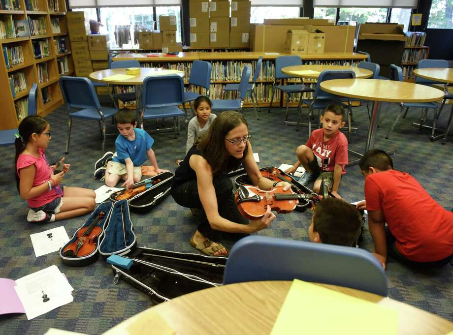 Nina Dryer teaches a third-grade violin class in the media center at New Lebanon School in the Byram section of Greenwich, Conn. Thursday, Sept. 17, 2015.  The school's building is overcrowded and the staff has had to make adjustments to deal with the overcrowdedness over the last several years. Photo: Tyler Sizemore / Hearst Connecticut Media / Greenwich Time